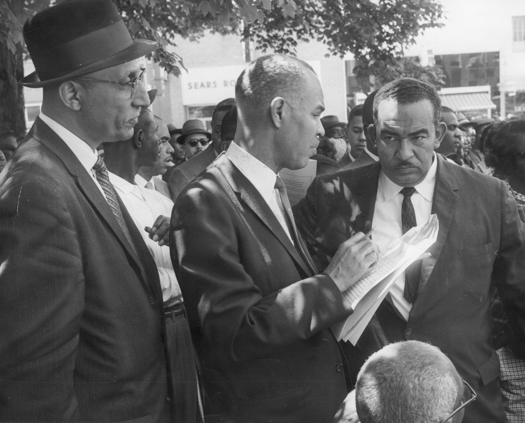 Black and white photograph of Oliver Hill, Roy Wilkins, and Reverend Francis L. Griffin speaking together at a Farmville demonstration.