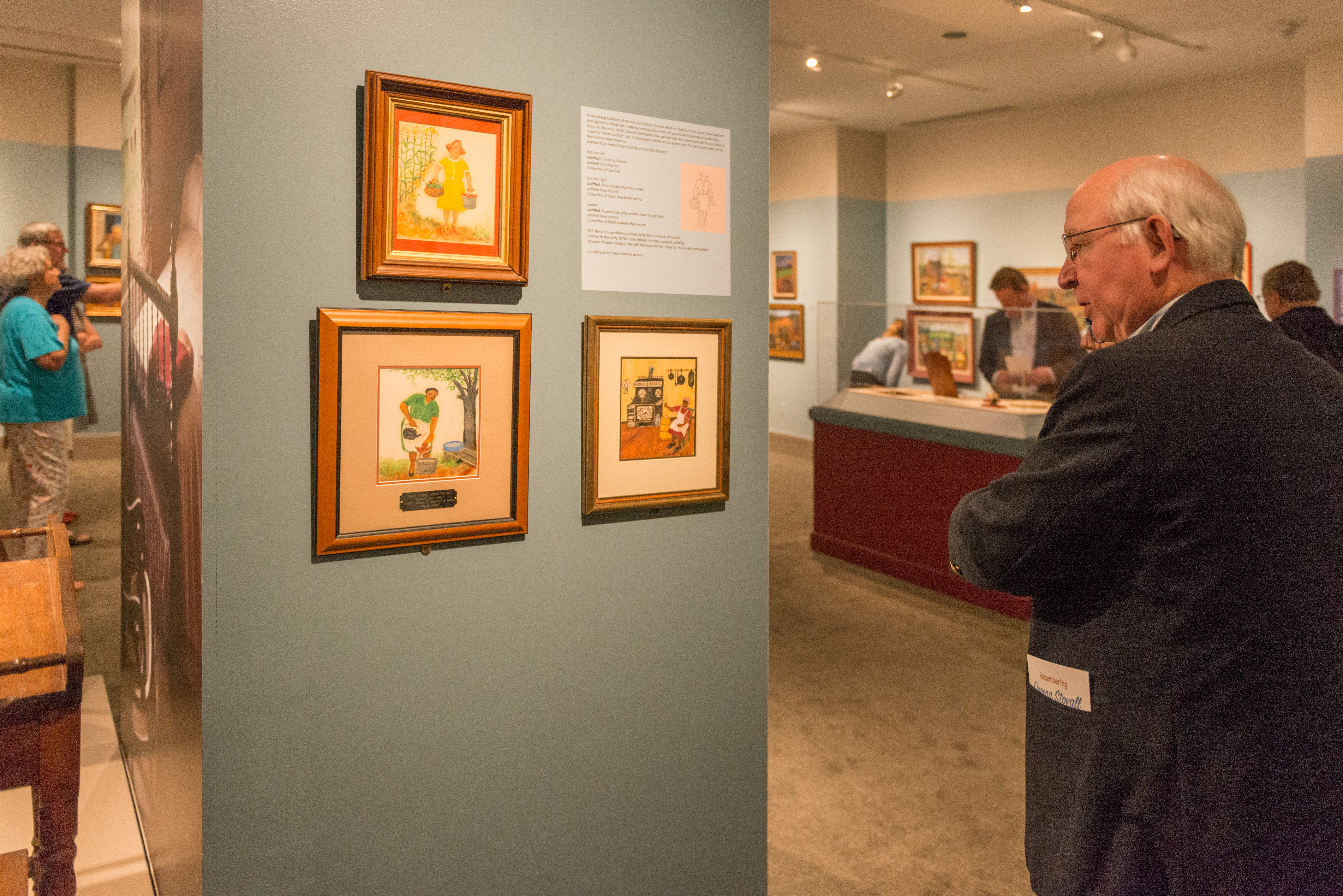 A member looks at paintings in the Queena Stovall exhibition