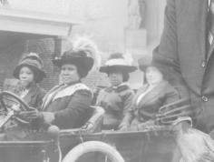 Historic black and white photo of 20th century black women in an open-topped car
