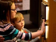 Two children touching a tactile component in The Story of Virginia, the long-term exhibition at VMHC.
