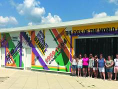A group of people stand in front of a mural with colorful lines and quotes.