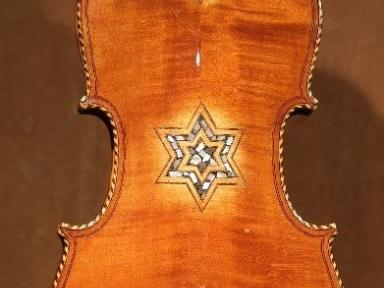 Back of restored klezmer violin dedicated to Wolf and Bunia Rabinowitz, a brother and sister, who played multiple concerts in the ghetto of Vilna during the Second World War. Both were killed with the last members of the ghetto.