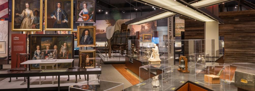 An interior gallery view with Colonial portraits and artifacts in glass cases.