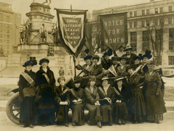 "Black and white photograph of women gathered in Capitol Square holding large banners which read ""Equal Suffrage League and Richmond, Virginia"" and ""Votes for Women."" Many otes for Women."""