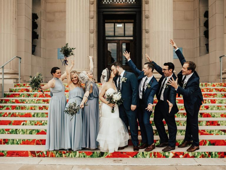 Bride, groom and wedding party pose on steps of the VMHC