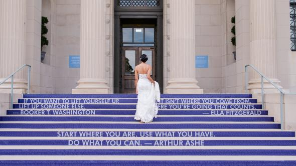 Bride walking up steps at VMHC. Steps have purple graphics with white words