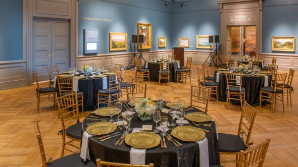 The Olsson Gallery at the VMHC with landscape paintings hanging on walls and dinner tables set for elegant party