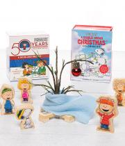 Peanuts character figurines surround a miniature Christmas tree with giant red ball ornament