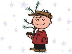 Charlie Brown holding a little tree in the snow
