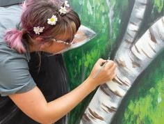 Nico Cathcart paints a depiction of a tree trunk