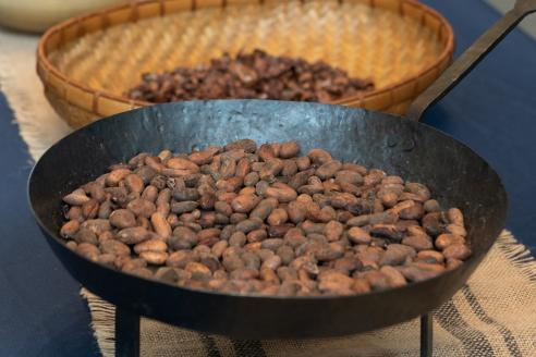 Cocoa beans in a cast iron pan in the foreground, with more beans in a basket in the background