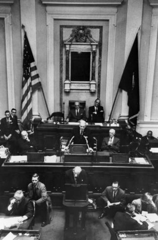 Black and white photograph of Governor J. Lindsay Almond standing in front of a podium addressing the General Assembly