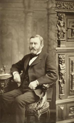 Vintage photograph of Ulysses S. Grant dressed in a suit and sitting in a chair at his desk