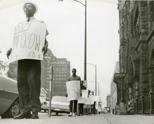 "Black and white photograph of an African American protestor with sign: ""Bury Jim Crow"""