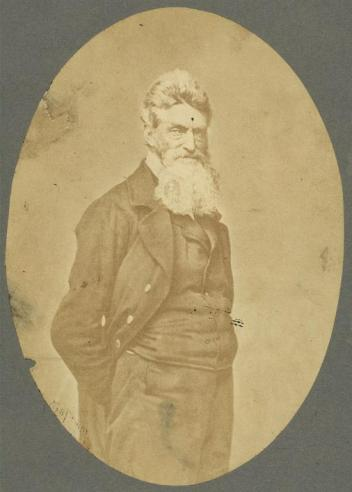Vintage photograph of John Brown standing with his hands in his pockets, looking toward the camera.