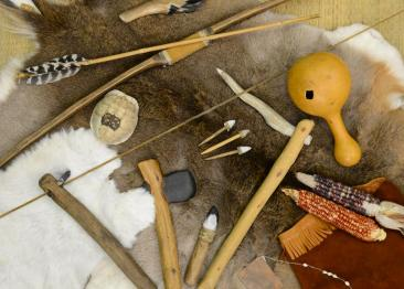 Native American tools and artifacts including corn husks, arrow heads, and feather bows