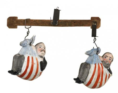 Ceramic figures of Harrison and Cleveland with each wrapped in an American flag and suspended from a wood beam