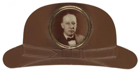A lapel pin in the shape of a brown derby hat with central photo of Al Smith