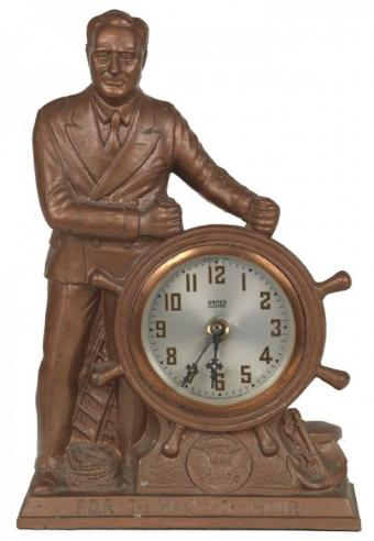 "A cast-metal clock with a figure of Franklin Roosevelt steering a ship's wheel, bearing the inscription ""F.D.R The Man of The Hour"""