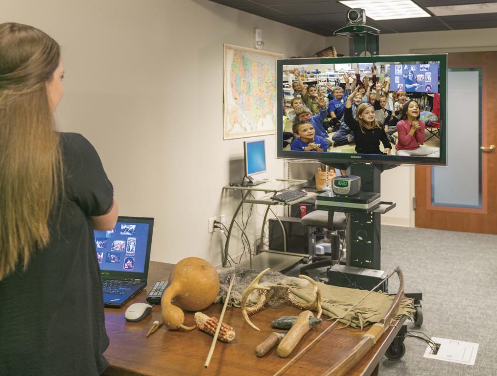 A museum educator conducting a virtual field trip in a studio