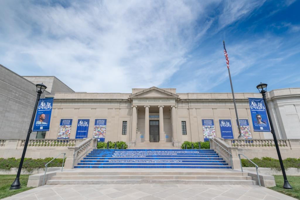 The front of the museum has multiple blue banners with multicolored collages and photos of the artists.