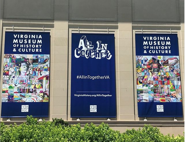 """Three banners on the museum's exterior wall depict multicolor collages of a woman's face, bees on bicycles, and other abstract shapes, with the words """"Virginia Museum of History & Culture"""" and  """"All In Together"""""""