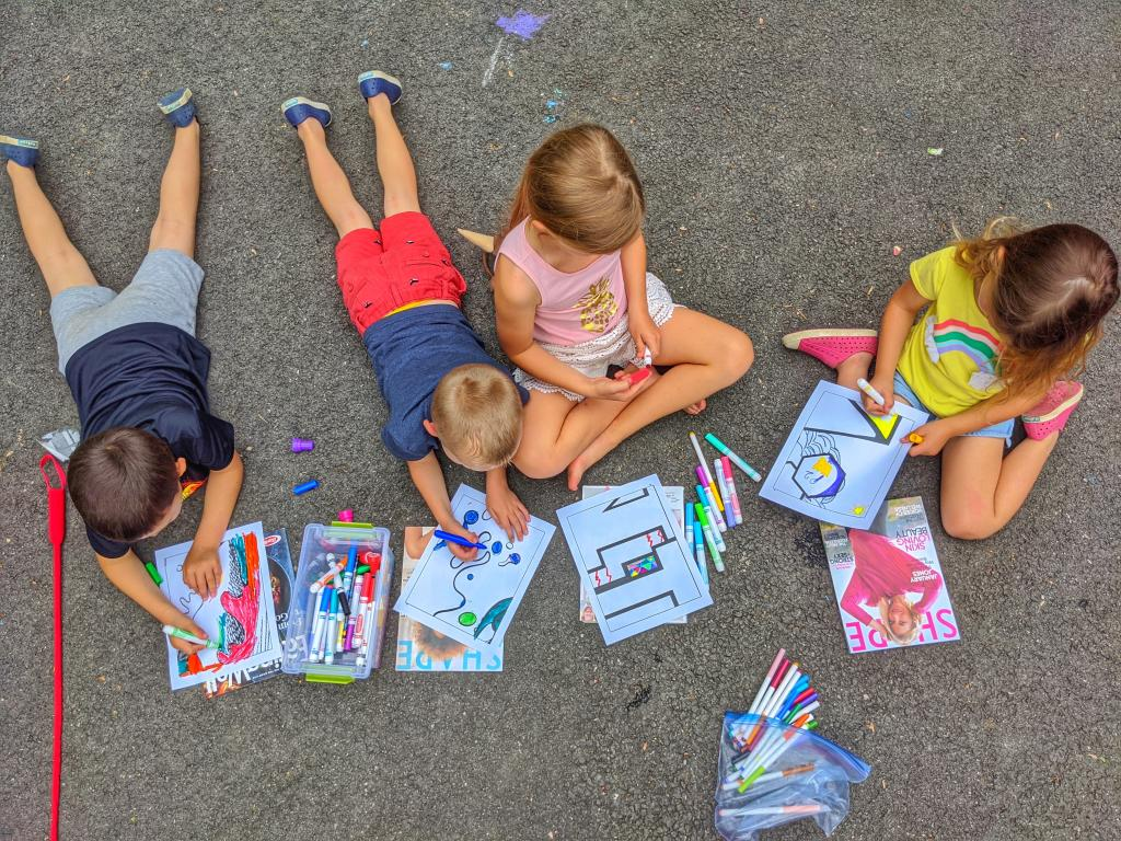 A group of children lays on the sidewalk coloring pages with multicolored markers.