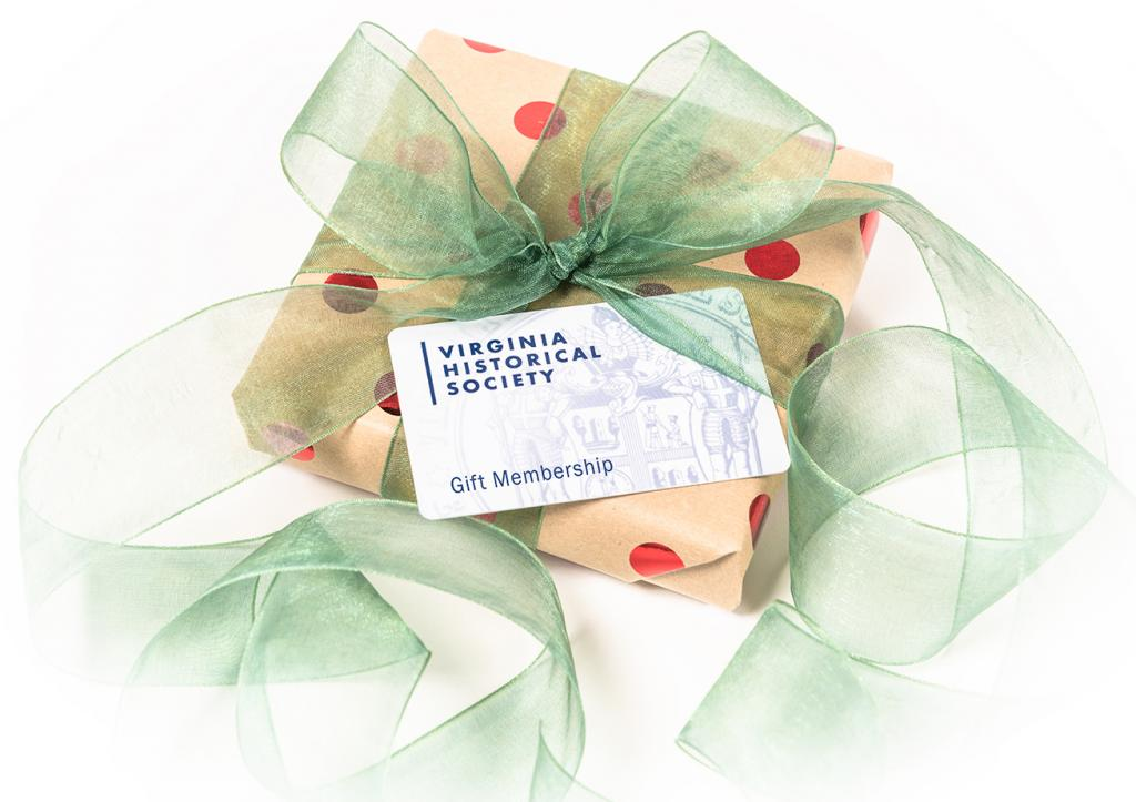 A gift membership card sits atop a wrapped gift with green ribbon.
