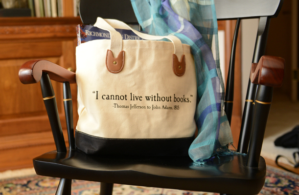 "A tote bag reading ""I Cannot Live Without Books - Thomas Jefferson"" sits on a chair with a scarf."