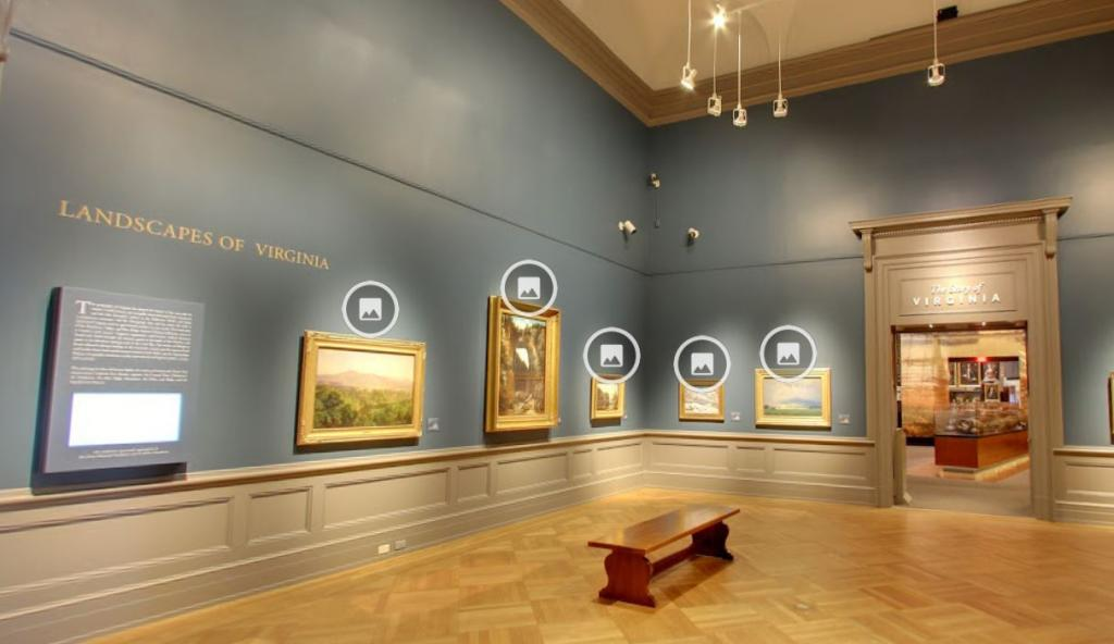 A gallery with wooden floors and blue walls, with gold-framed landscape paintings on the walls.