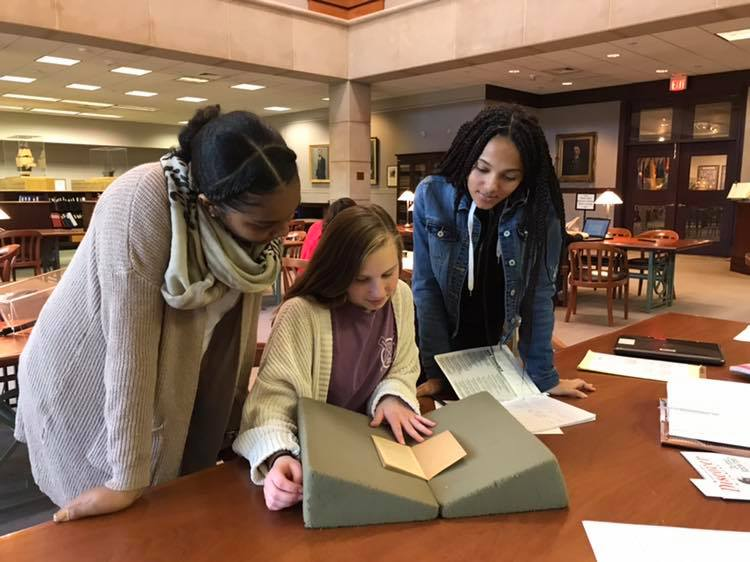 Students analyze a book in the library